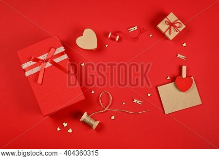 Frame Of Valentine Gifts, Red Giftbox, Hearts, Twine, Clothespins And Brown Paper Card On Red Backgr