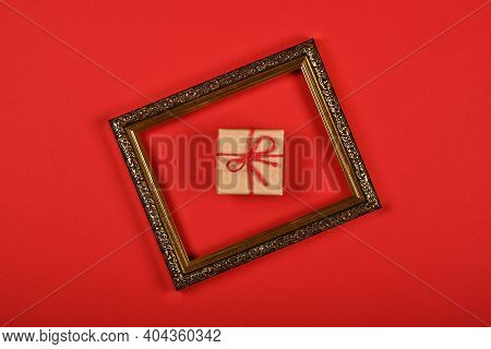 Close Up One Brown Paper Giftbox In Golden Frame Over Red Background, Flat Lay, Elevated Top View, D