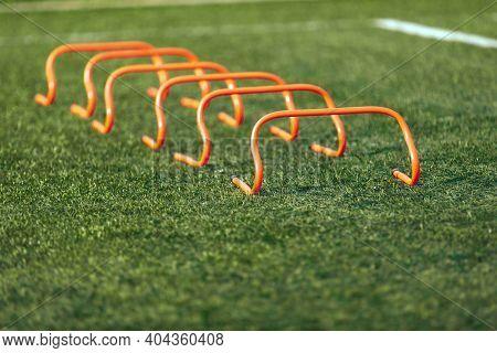 Set Of Soccer Hurdles. Orange Football Hurdles Training. Grass Practice Field
