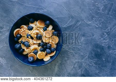 Close- Up Mini Pancake Cereal, Mini Pancakes In A Dark Blue Bowl With Sirup Honey With Blueberry