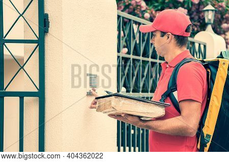 Concentrated Postman Ringing Doorbell And Holding Parcel And Clipboard. Handsome Courier In Red Unif