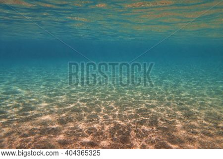 Underwater View, Sandy Sea Bottom And Transparent Water. Life-giving Sunlight Underwater.