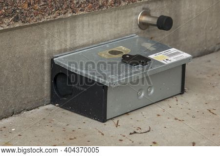 Bonnerup, Denmark - 15 Juli 2020: Grey Metal External Rodent Rat Bait Station Outside Against A Bric