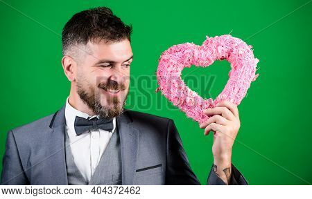 Hipster Hold Heart Symbol Love. Man Formal Suit Celebrate Valentines Day Green Background. Spread Lo