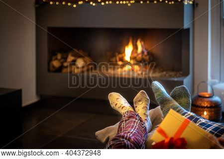 Couple Sitting In Front Of The Fireplace Relaxes With The Warm Fire By Warming Their Feet. Concept O