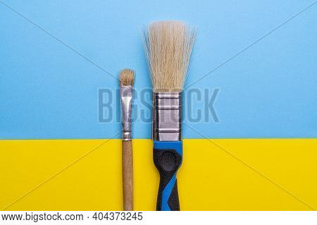 A Large And A Small Brush Placed Side By Side On A Colored Surface