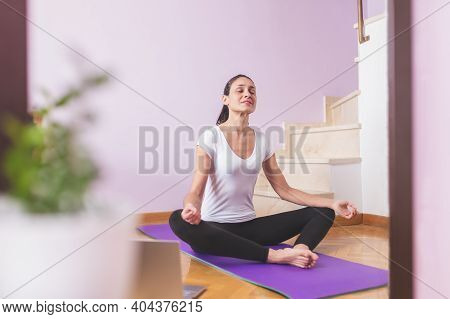 Young Happy Caucasian Woman, Meditating In The Living Room While Looking At Her Laptop. Health Care