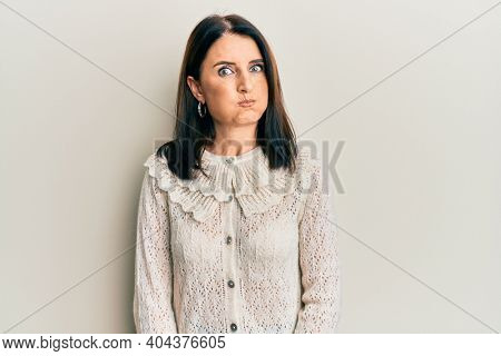 Middle age brunette woman wearing casual clothes puffing cheeks with funny face. mouth inflated with air, crazy expression.