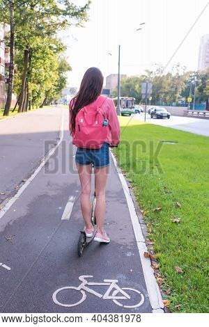 Woman Rides A Scooter In City In Summer, A View From Back, Denim Shorts And A Pink Jacket With A Bac