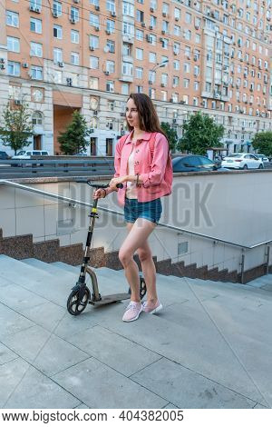 Woman In Summer In City Goes To Underground Passage With A Scooter, Denim Shorts And A Pink Jacket W