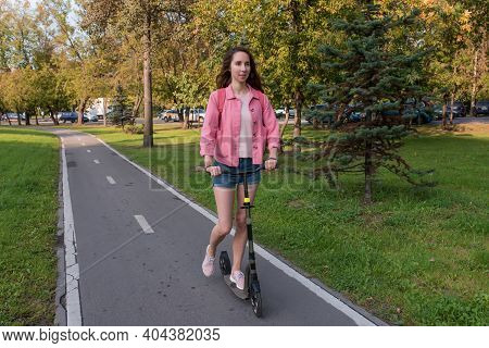 Woman In Summer In City Rides A Scooter On A Bike Path, Background Road Trees Green Grass And Spruce