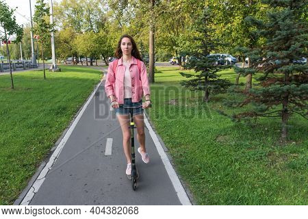 Woman In Summer In City Rides A Scooter On A Bicycle Path, In Motion, Background Road Trees Green Gr