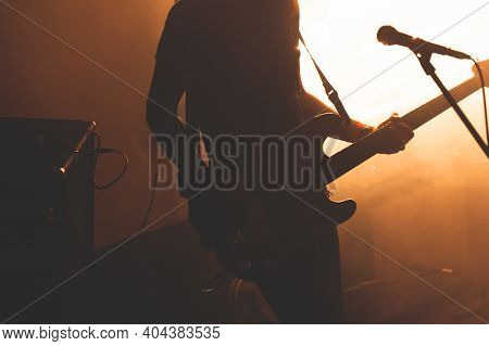 Silhouette Of Bass Guitar Player With Microphone In Bright Warm Illumination, Live Music Theme
