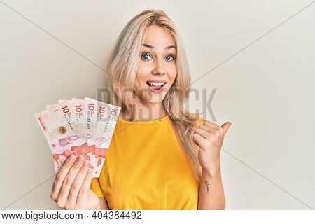 Beautiful caucasian blonde girl holding 10 colombian pesos banknotes pointing thumb up to the side smiling happy with open mouth