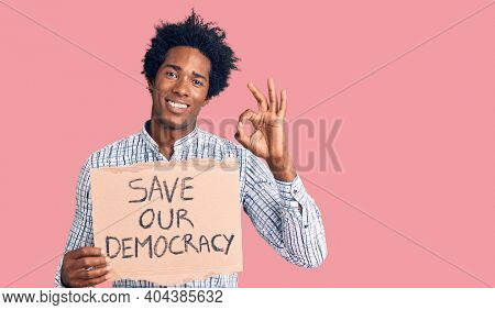 Handsome african american man with afro hair holding save our democracy protest banner doing ok sign with fingers, smiling friendly gesturing excellent symbol