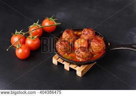 Stewed Meatballs In Tomato Sauce In A Pan On A Wooden Coasters On A Dark Background.