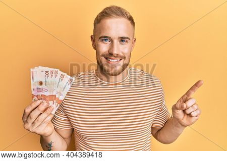 Young caucasian man holding 10 colombian pesos banknotes smiling happy pointing with hand and finger to the side