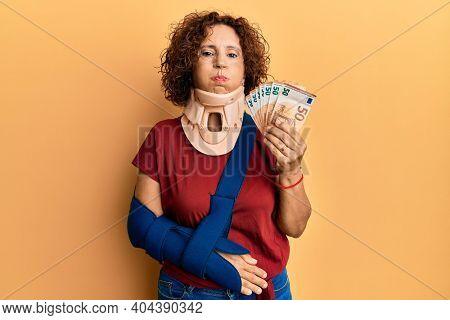 Beautiful middle age mature woman wearing cervical collar and sling holding insurance euros puffing cheeks with funny face. mouth inflated with air, catching air.