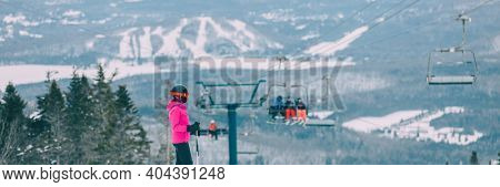 Skier woman athlete going skiing from slope summit mountain top with view of the landscape and skiers on ski lift background. Winter sports active lifestyle banner.