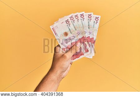 Hand of hispanic man holding colombian 10 pesos banknotes over isolated yellow background.