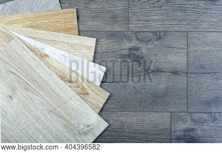 Vinyl And Linoleum Samples On A Wooden Background. Vinyl For Flooring With Wood Grain Texture And Pa