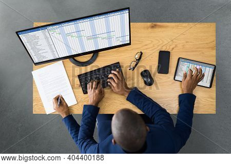Tired Young African Man Doing Multitasking Work On Laptop In Office
