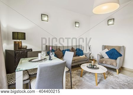 Illuminated Living Room Interior With Sofa And Table