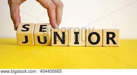 From Junior To Senior Symbol. Businessman Turns Cubes And Changes The Word 'junior' To 'senior'. Bea