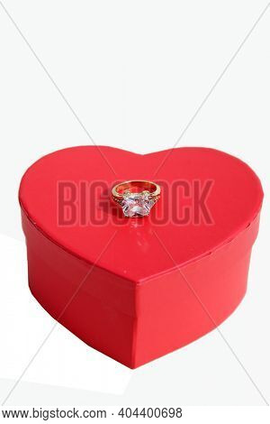 Valentines Day. Wedding Ring with a Red Valentines Day Heart. Engagement Ring in a Red Ring Box with a Red Heart. Isolated on white. Room for text. Happy Valentines Day.