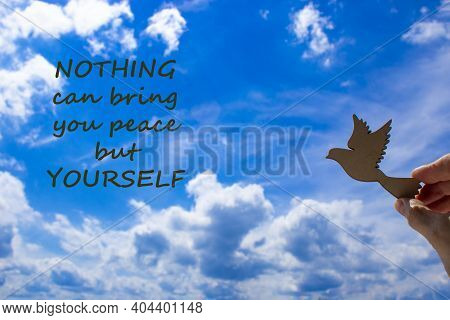 Man Hand Holding Wooden Bird On Cloud Sky Background. Words 'nothing Can Bring You Peace But Yoursel