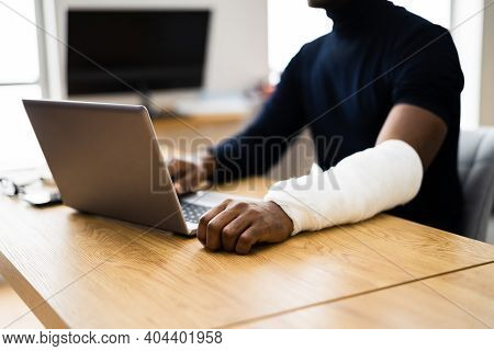 Injured Worker Compensation. Broken Arm African Man On Computer