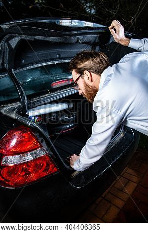 Young Adult Man Looking Into A Car Trunk At Night.