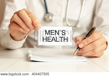 Mens Health. Doctor Holds A Business Card In Her Hand. Text Is On The Sign. Medicine Concept