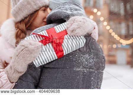 Young Woman Wraps Her Hands Around Her Boyfriends Neck Holding Being Happy Because Of A Present For