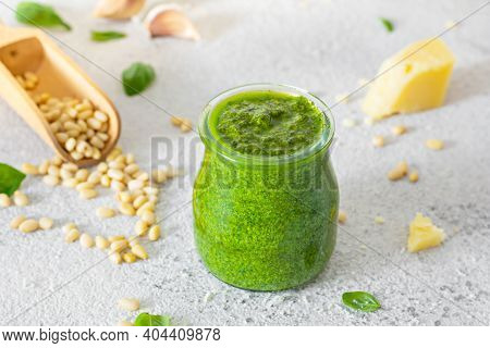 Green Pesto In A Glass Jar Made From Fresh Basil Leaves, Pine Nuts, Parmesan, Garlic And Olive Olia