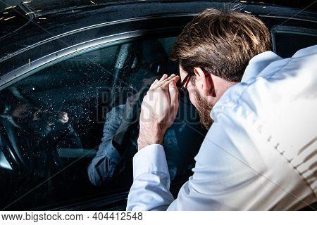 Man Looking Through A Side Window Into A Car. Locked Keys Inside The Car.