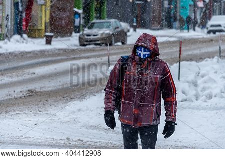 Montreal, Ca - 21 January 2021: Man With Quebec Flag Face Mask For Protection From Covid-19 Walking