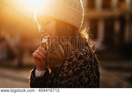 Laughing Blissful Girl Posing In Sunny Autumn Day. Outdoor Photo Of Charming Lady In Trendy Coat.