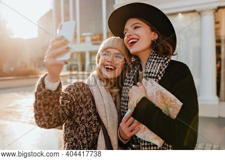 Glad Girl Using Phone For Selfie On The Street. Appealing Ladies Exploring City In Autumn Day.