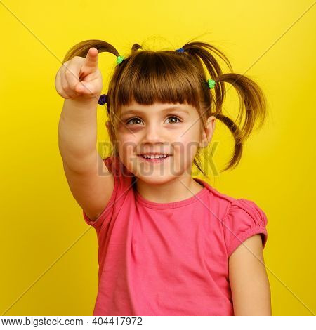 Portrait Of Smiling Little Caucasian Girl With Pigtails And Bruise Under The Eye And Pointing Up Wit