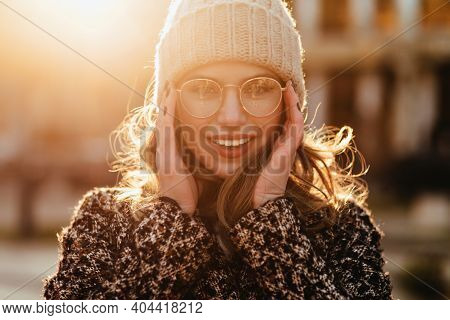 Outdoor Portrait Of Good-humoured Woman Wears Coat In Spring. Gorgeous European Girl Walking Down Th
