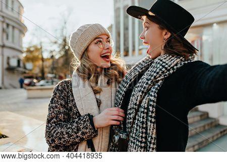 Carefree Girl In Black Coat Making Selfie With Sister. Good-humoured Female Friends Walking Around C