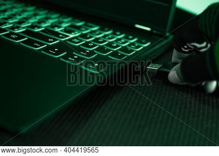 Identity Theft Or Cyber Security Concept. Hand Hacker Usb Flash Drive Plug In To Laptop For Data The