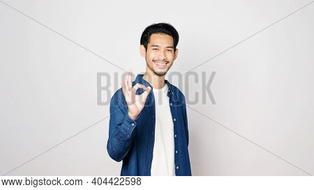 Young Asian Man Showing Ok Hand Sign And Smiling While Standing Over Isolated Grey Background, Happy
