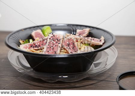 Seared Tuna Salad With Lettuce, Sliced Green Bell Pepper, And Red Onion On A Wooden Table Next To Br