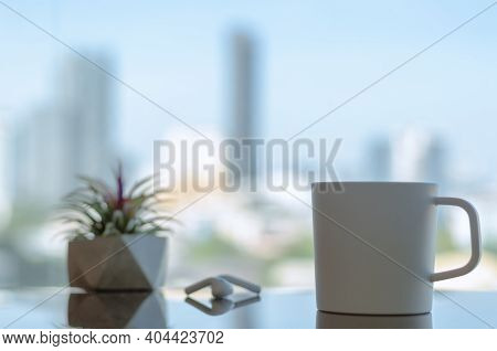 White Coffee Cup With Ear Phone And Air Plant Tillandsia With Blurred City Background In The Morning