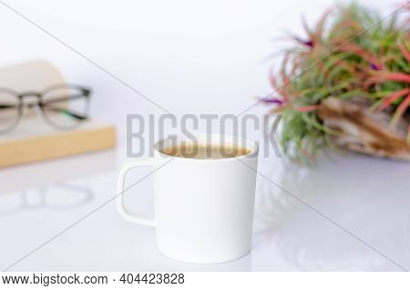 A Cup Of Coffee On Table With Air Plant Tillandsia, Spectacles And Book On White Background.