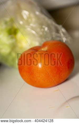 Uncut Tomato In Front Of An Out Of Focus Head Of Lettuce