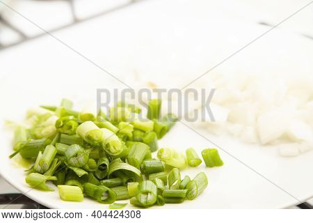 Chopped Green Onion And Diced White Onion On A White Plate