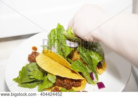 Woman Preparing Three Tacos, Putting Romaine Lettuce In The Shells At Home